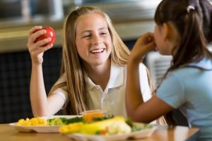 Two girls eating lunch at school