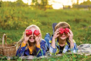 Two Kids put apples against their eyes
